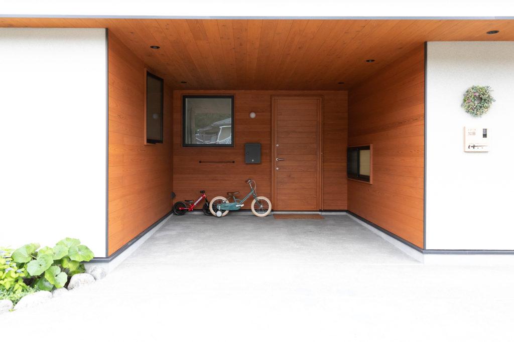 ひのきの玄関ドアは実は既製品。ドアの色に合わせて杉板を塗り、玄関を囲むように貼り付けた。駐車スペースとしても活用。雨の日には濡れずに荷物を出し入れできる。