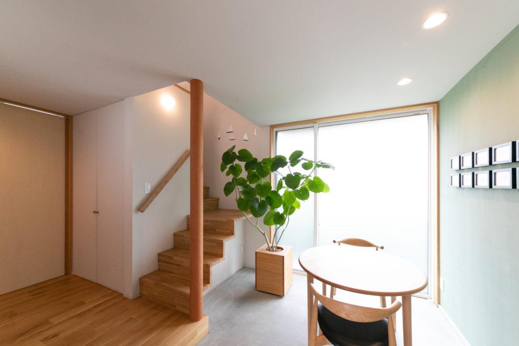 玄関を開けると、可愛らしい打ち合わせスペースがある。ウンベラータの緑が心地よい。左側は居住スペース、右側がアトリエへ。