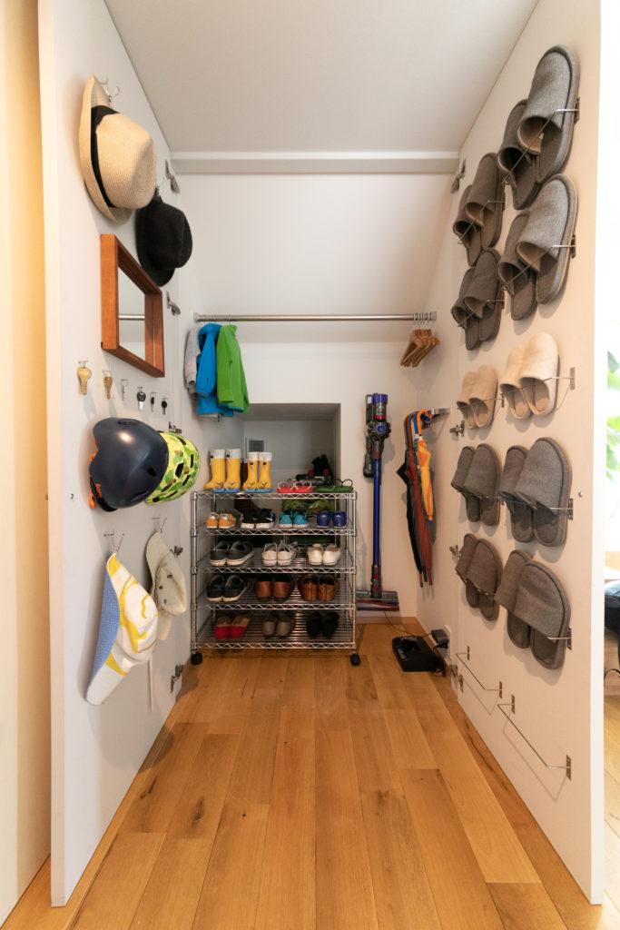 階段下の収納。頻繁に使う靴やスリッパ、コートなどを収納。靴を干すときは什器ごと外に出すことができる。24時間換気をしているため、臭いもこもらない。