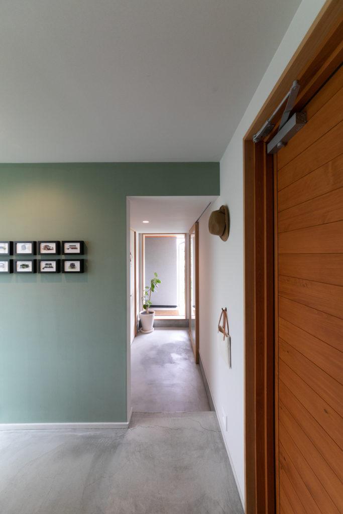 一段下がった奥がアトリエへと続く。緑色の壁は加藤さん夫妻で塗った。ディスプレイされた帽子とバッグは景さんが日常的に使用するもの。