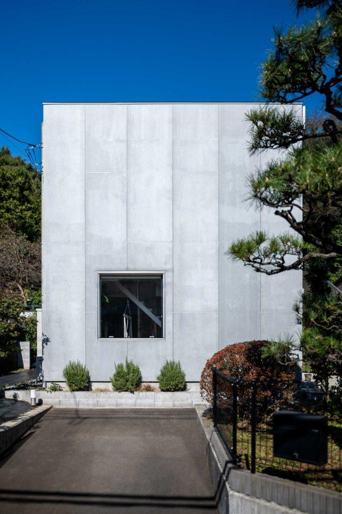 鈴木邸のアプローチ。外装材は窯業系サイディングを裏返しにしたものに撥水材を塗って使用している。