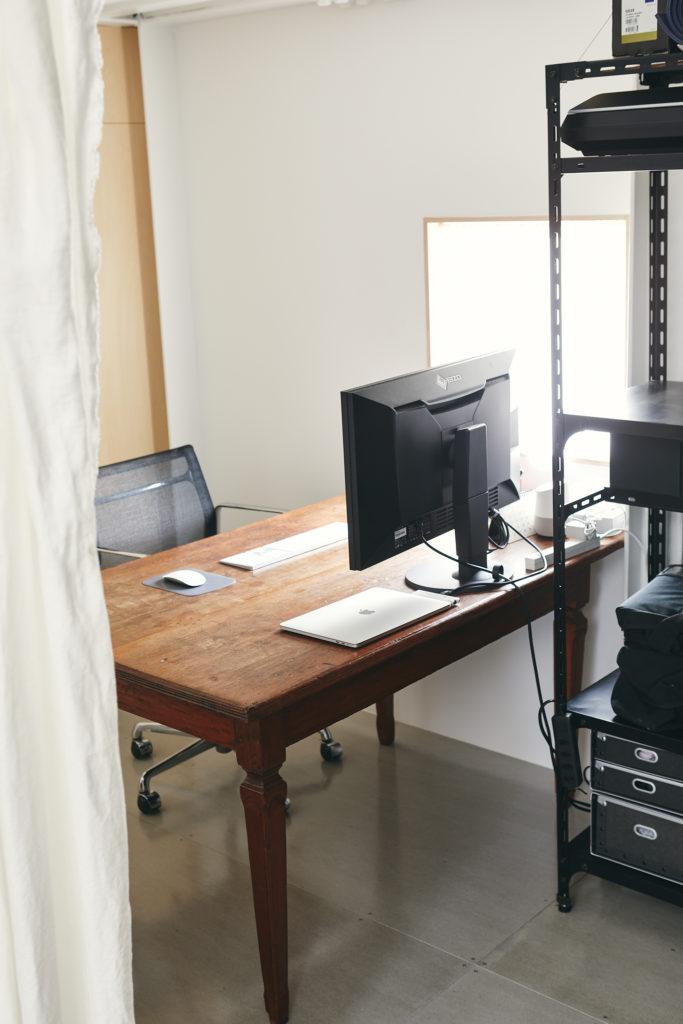 柳原さんのワークスペースは2階に。アンティークのテーブルに布のカーテンが温かみを添える。