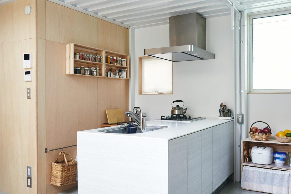 両側に収納のあるペニンシュラキッチンはサンワカンパニーで。夫が料理を担当して柳原さんがサポート。2人で作業するので、両側から使えて便利なのだそう。床上の収納はリンゴ箱でDIYしたもの。