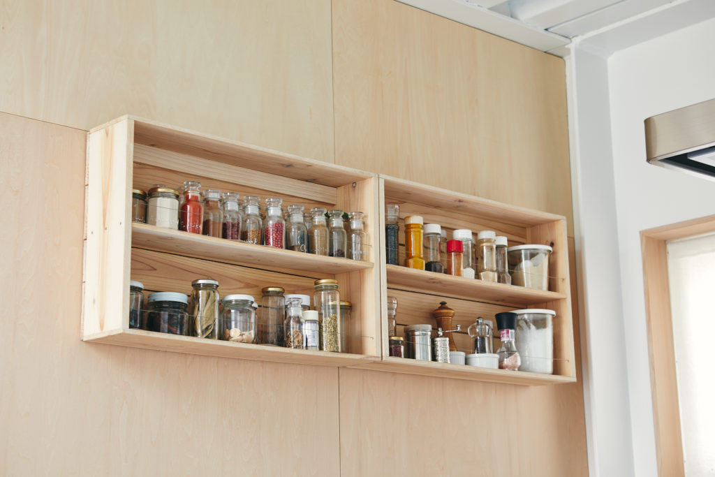 壁にかけたスパイスなどの収納棚は、海産物を入れるトロ箱を活かしてDIY。