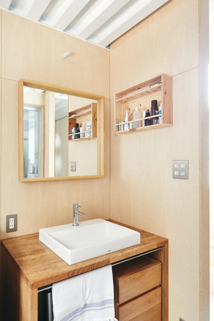 無垢の素材がシンプルな空間になじむ洗面台。壁づけの棚はワイン箱で。