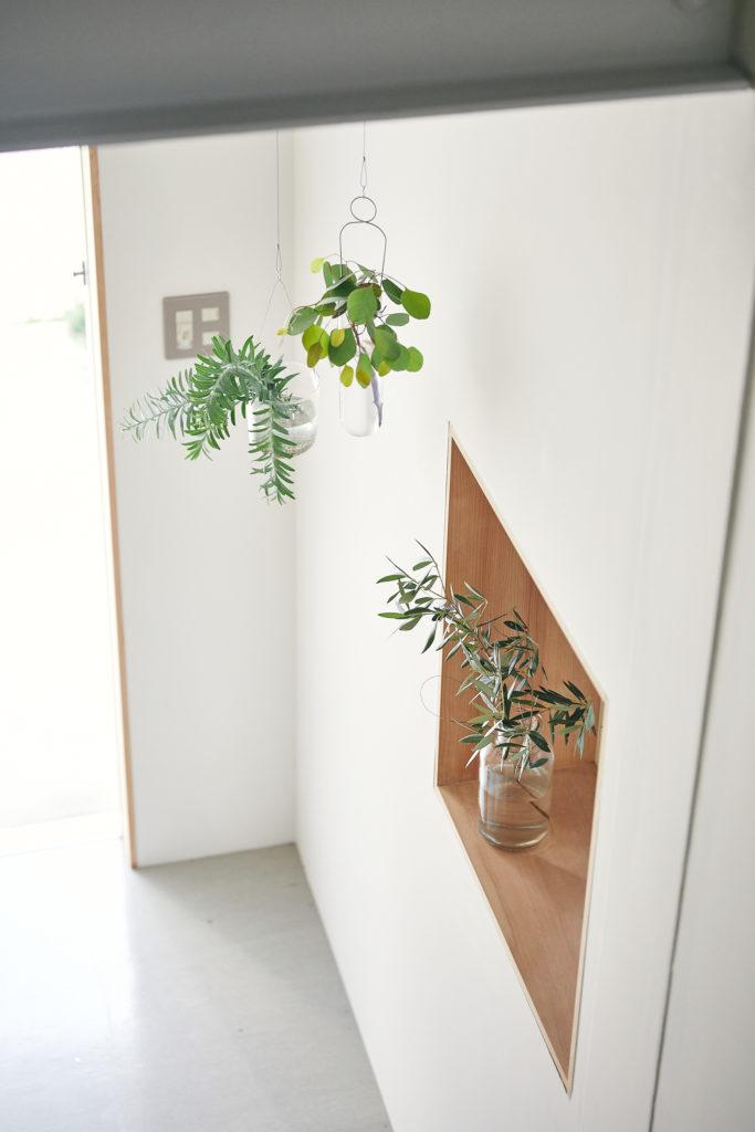 """玄関も屋上ガーデンで育てたグリーンがお出迎え。窓枠の木も""""バトン""""で仕上げている。"""