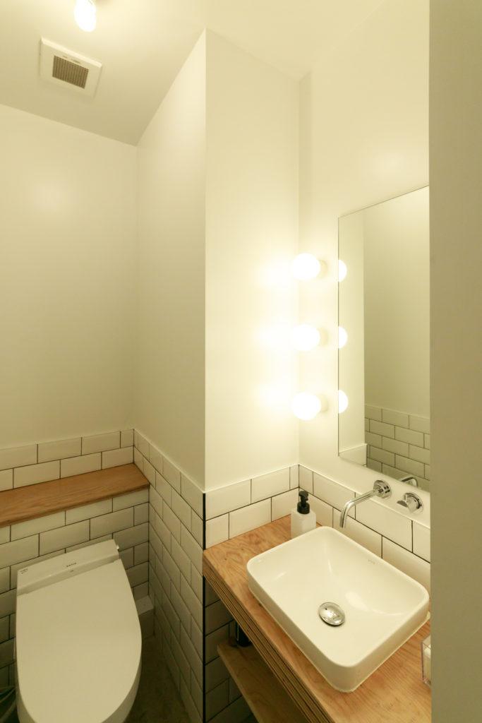 トイレの鏡には女優ライトが。「既存の照明器具を6つ配置しています」。2階の洗面所の鏡も同様の仕様。