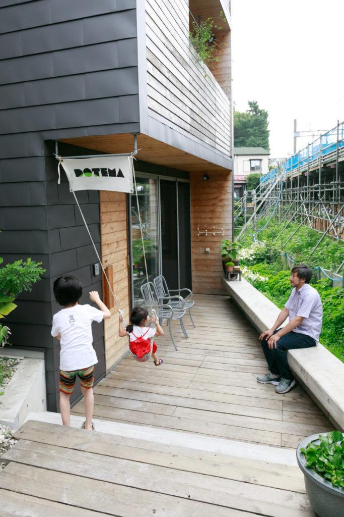 敷地の奥が自邸と『DOTEMA』。ウッドデッキではバーベキューを楽しむ。コンクリートの擁壁はコの字に曲げてベンチとして使えるようにしている。