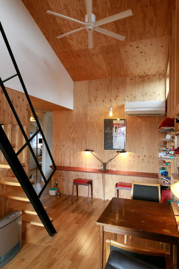 2階のリビングはたっぷりとした天井高。針葉樹合板の壁がくつろげる雰囲気。