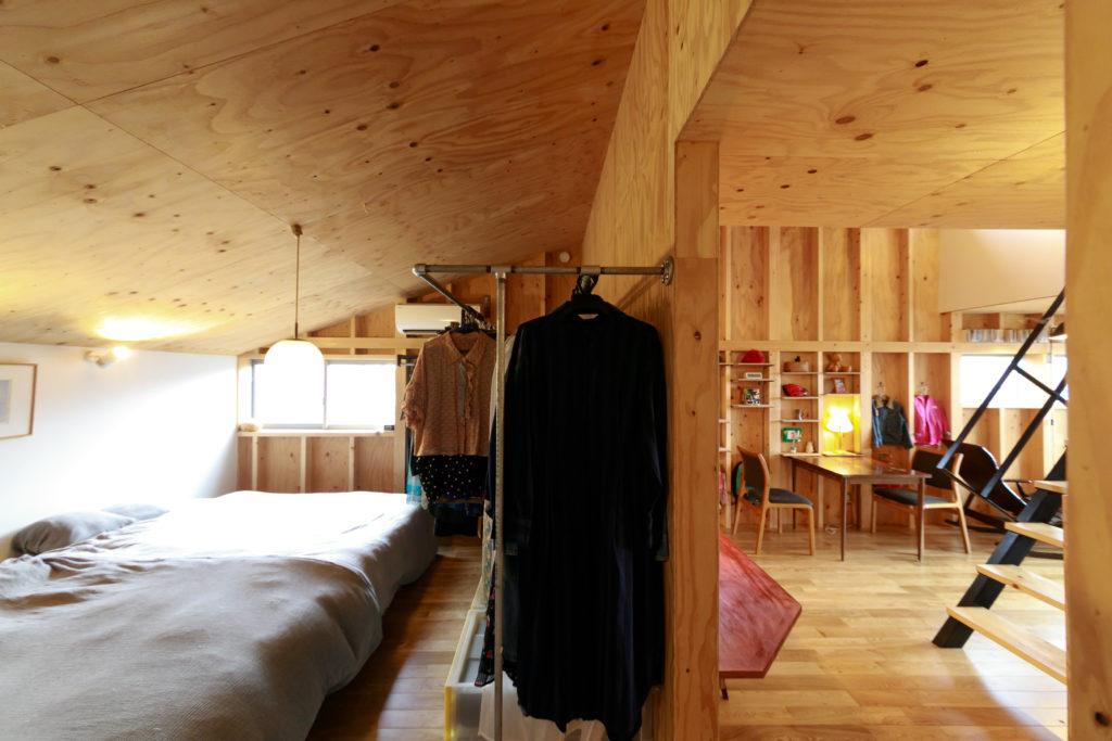 右側がリビング、左側が寝室。扉はつけず、壁でゆるやかに仕切っている。水道管で作ったラックに家族の服を収納。