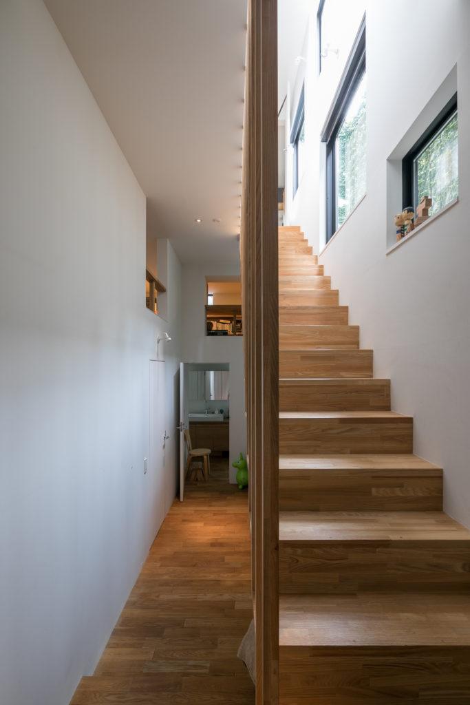 玄関を入って、左を向くとホールとなっている。突き当たりには水回り、左には寝室がある。北側にあたる右の階段の側壁には大小さまざまな窓が設けられ、外壁に挟まれた中庭からの光が取り込める。