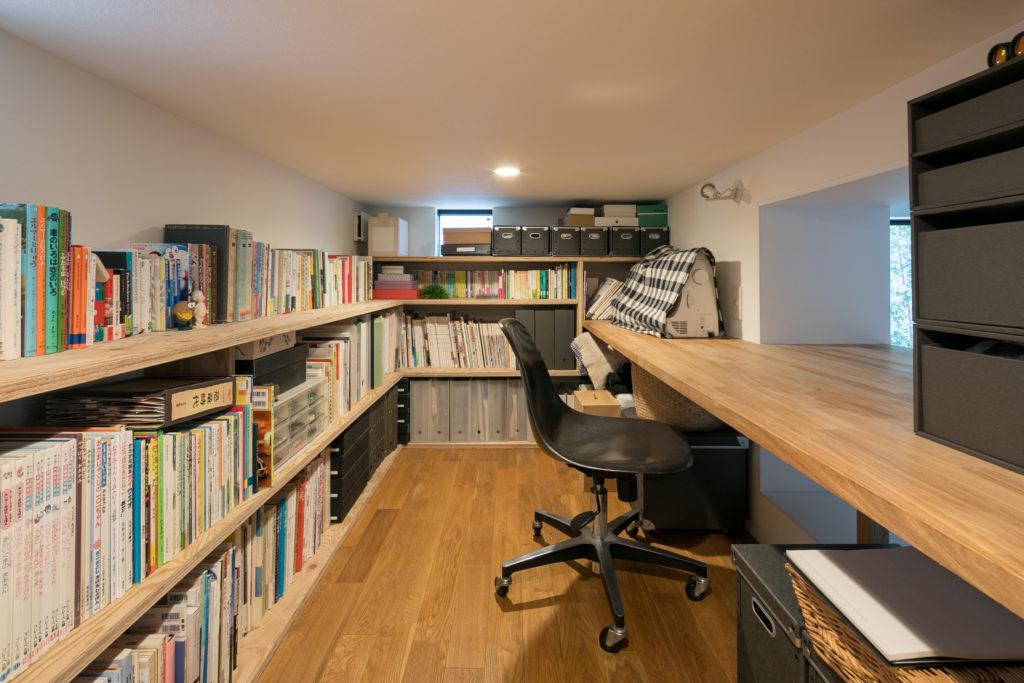 作り付けの棚には本がずらり。同じく作り付けの机は、主に岸さんの裁縫スペース。正面からは1階全体を望むことができる。