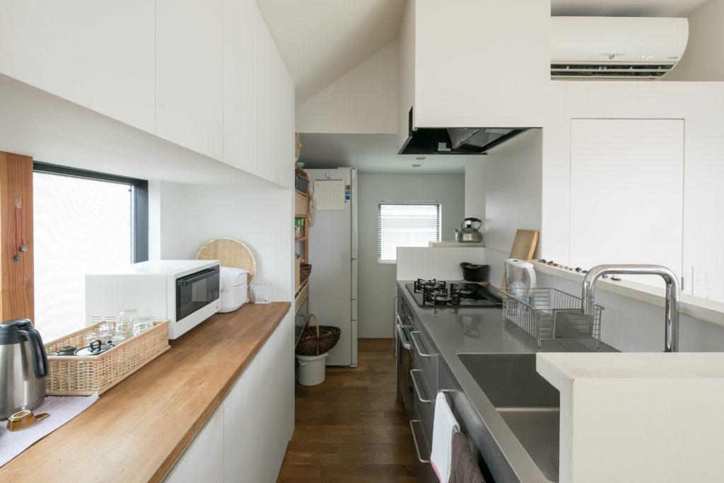 キッチンの配置やカラーリングは、岸さんと猿田さんが相談して決めた。手前の作業台は、窓を出窓にすることで生まれた。