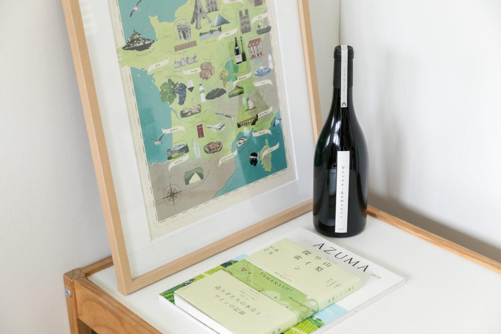 手がけた仕事には、ワインカタログやワインラベルのデザインも。額縁に飾られているポスターは、ワインの産地が描かれており、デザインは中川さん、イラストは岸さんが担当した。
