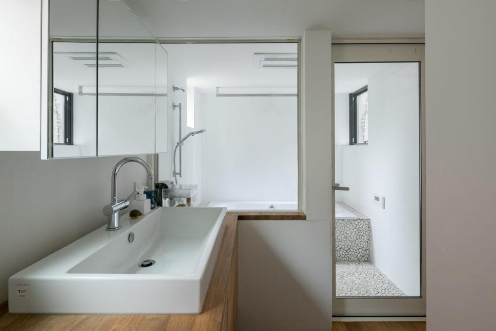 1階の水回り。浴室と洗面を仕切るガラス窓によって、視線が抜ける開放的な空間に。