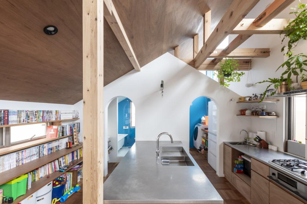 キッチンの奥に立つ壁の家型がとても印象的。キッチンのカウンターは映像系の仕事をされている奥さんの仕事机、子どもたちの勉強机としても使用される。右奥の洗濯スペースと浴室とキッチンがこのカウンターを中心に回遊できる。