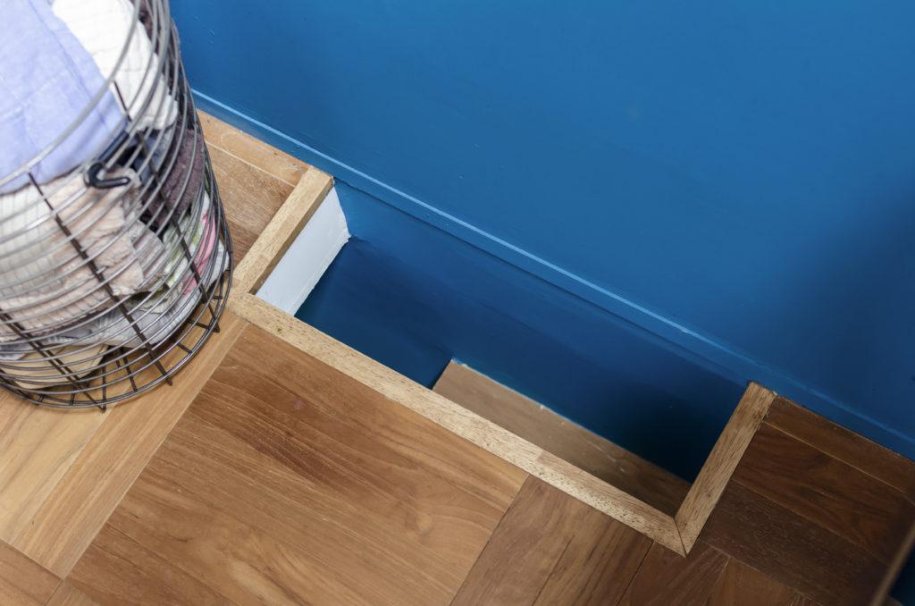 2階の床に開けられたネコ用の穴。青い壁が1・2階とつながっているのがわかる。