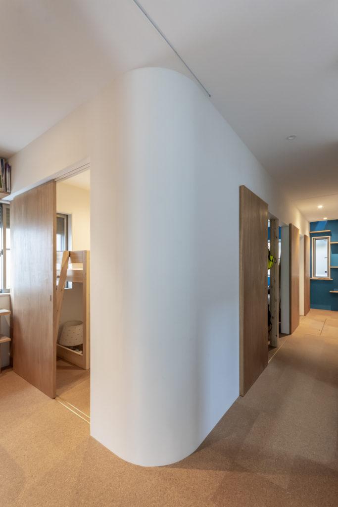 壁のコーナー部のアールが左右の空間を柔らかにつなげて広がり感を出している。手前が子ども部屋で奥が主寝室。