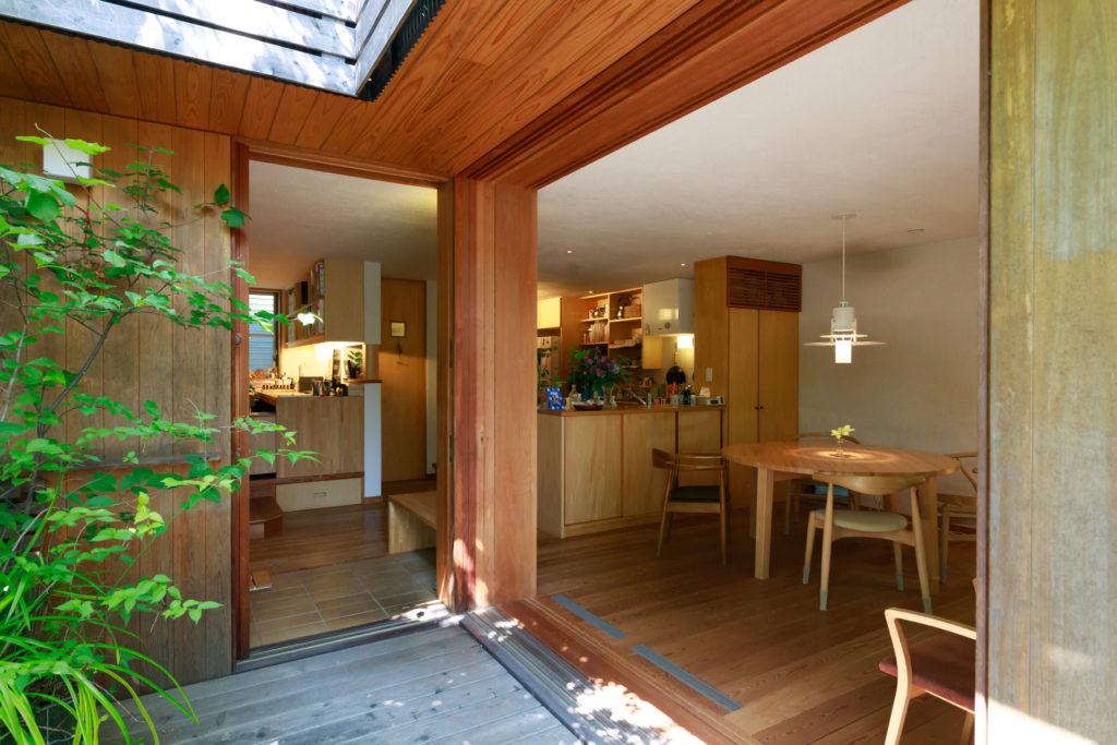 独立した玄関は設けず、中庭からそのままリビング・ダイニングへ入ることも。右奥には対面キッチン、左奥は新井さんの仕事スペースがある。