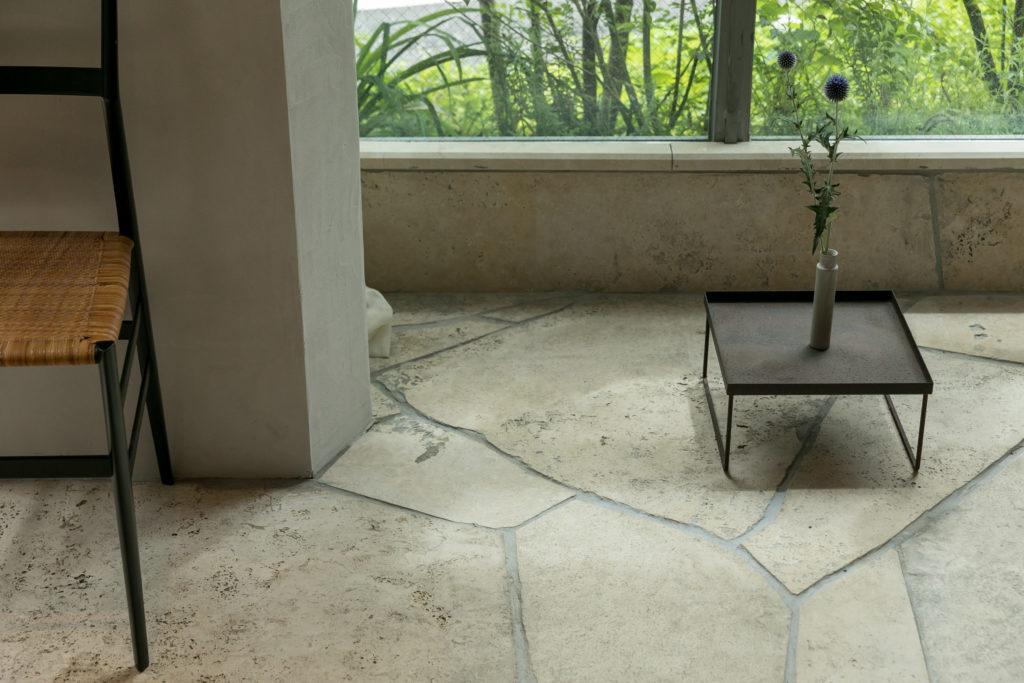 アプローチから室内へと連続する床のトラバーチンはあえて磨いていない裏面を表にして張り、ナチュラルな表情を楽しむ。