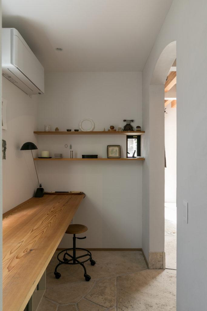 作業台は壁付に。棚の間に玄関を伺える小窓をつけた。