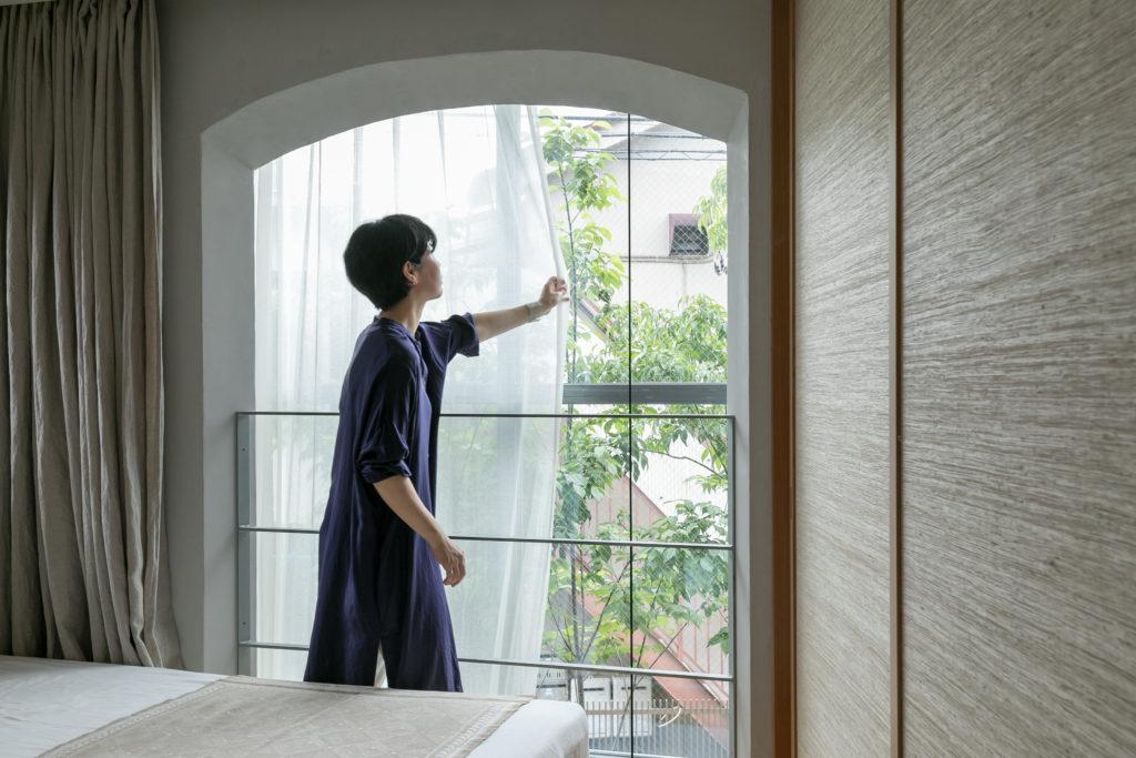 「吹き抜けのカーテンは1階までの長さがあります。キレイな透け感のある生地を探し、自分で縫いました」。手前はリネンのカーテン。