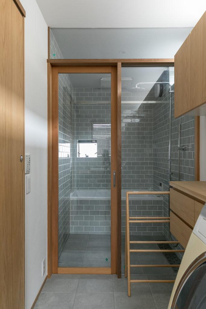バスルームの扉は木で造作。グレーのタイルが美しい。シャワーはグローエ社のもの。