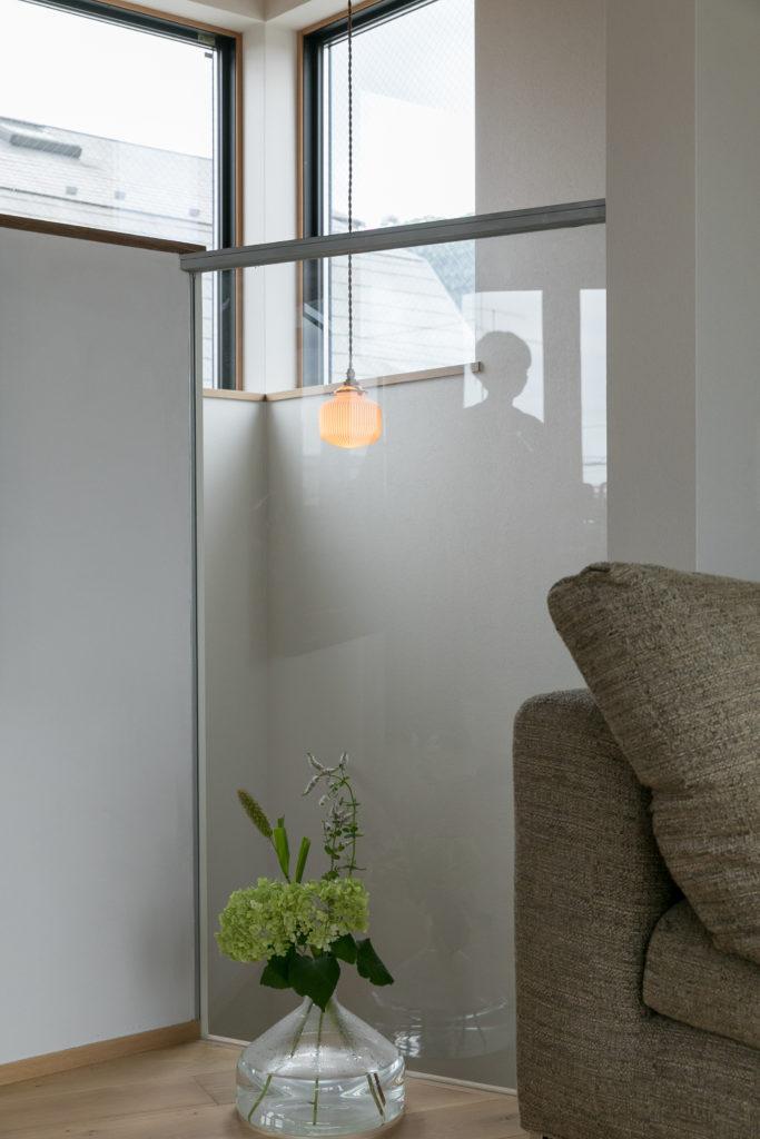 階段の壁は一部ガラスにすることで、リビングからも照明器具の明かりを楽しむことができる。「飛松灯器のペンダントライトは、ぽっかりと浮かぶお月さまのようで気に入っています」