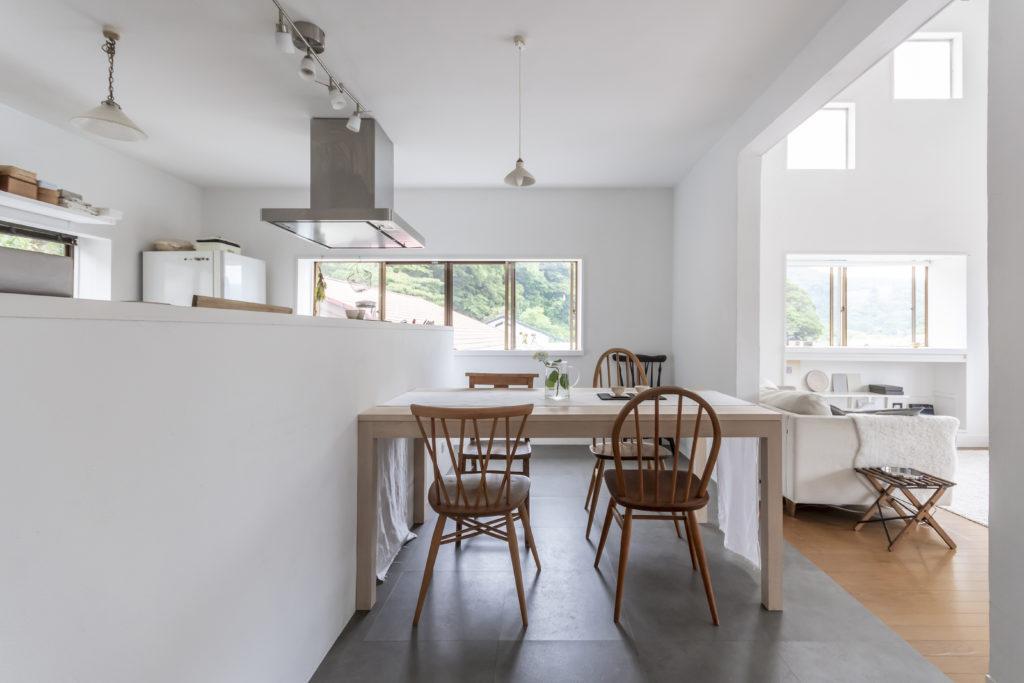 キッチン台に腰壁が設けられた、アイランドキッチン。無垢のメープル材を使ったダイニングテーブルは、岐阜の「RITON」に出向いてオーダーしたもの。