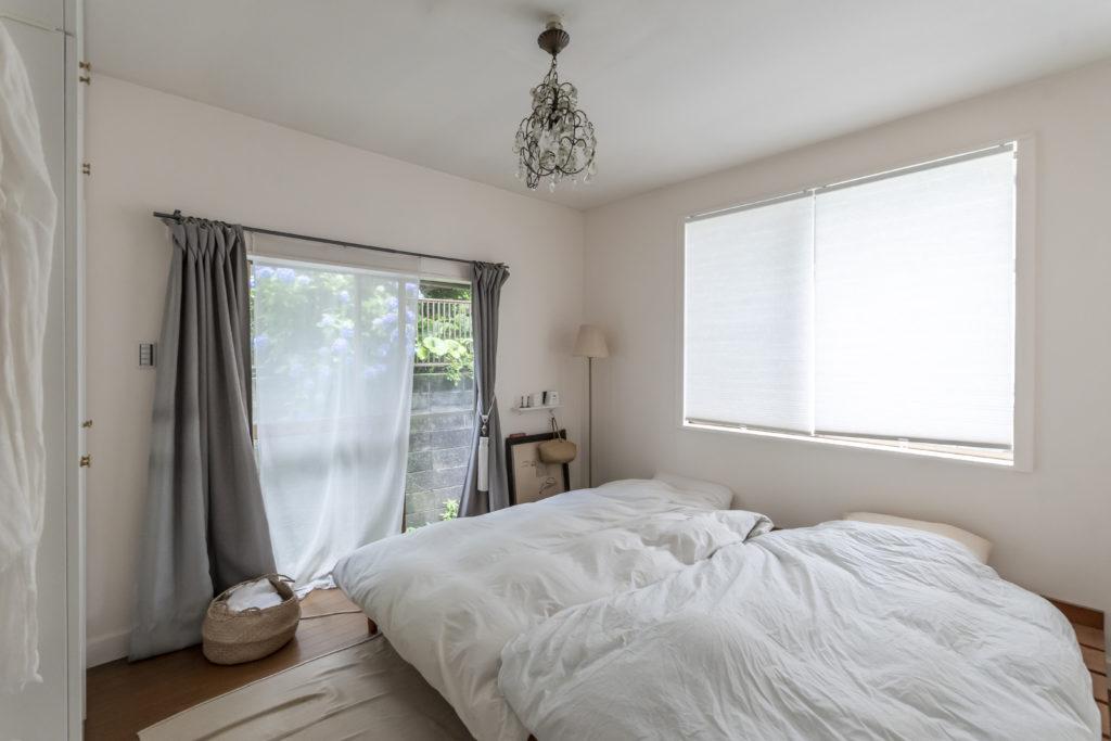 隣家の庭が借景になるベッドルーム。壁はすべて白く塗装した。