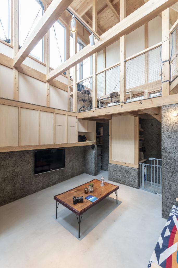 階段を上がったところからリビングを見る。左の壁と奥の壁は擁壁がそのまま室内の壁として使われている。