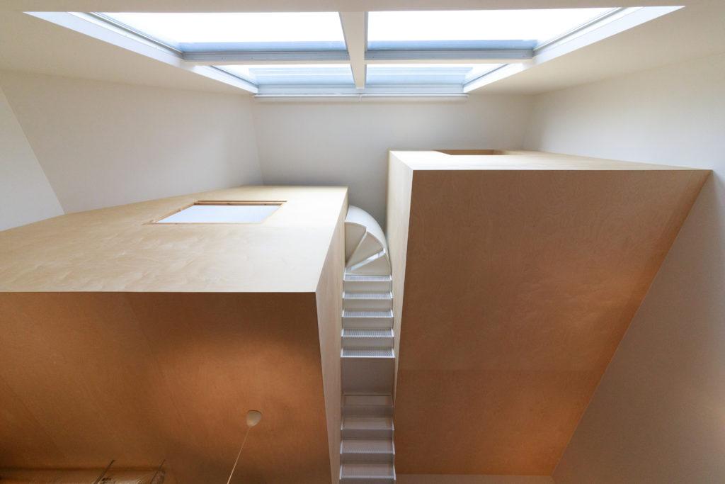 2階から3階を見上げる。大きな白い吹き抜けの大空間に、四角いバーチ合板の箱がポッカリと浮かび、白い階段がふたつの箱をつなぐ。左右の箱の高さや長さが違うのも楽しい。左側の箱の上部にはロフトもある。