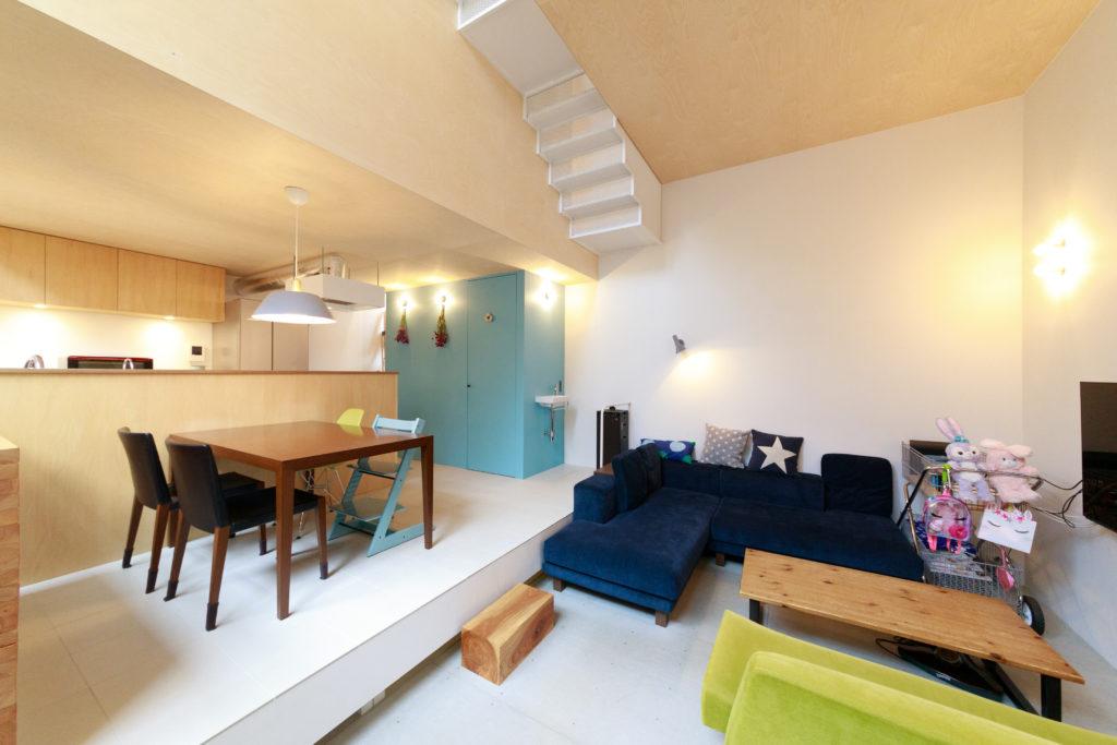 リビングとダイニングキッチンの天井の高さを変え、段差もつけている。「家具は以前使っていたものが多いですが、ブルーのL字型のソファはソファ専門店NOYESで購入しました」