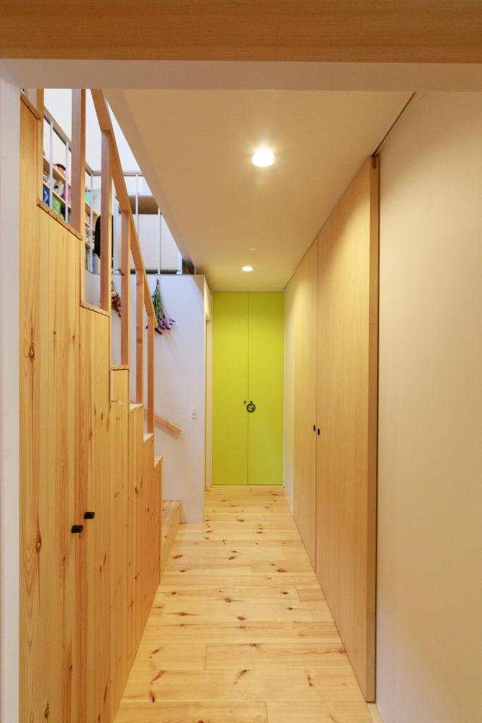 玄関を入ると視線の先に明るいグリーンの扉が出迎える。階段下は収納になっている。