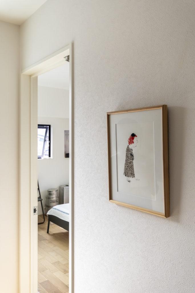 ベッドルームの入り口には、イラストレーター寺坂耕一さんの描いた絵を飾って。