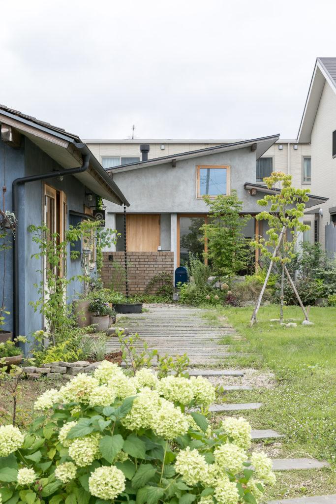 アプローチから工藤さんの家を見る。左手のブルーの建物はアトリエ。
