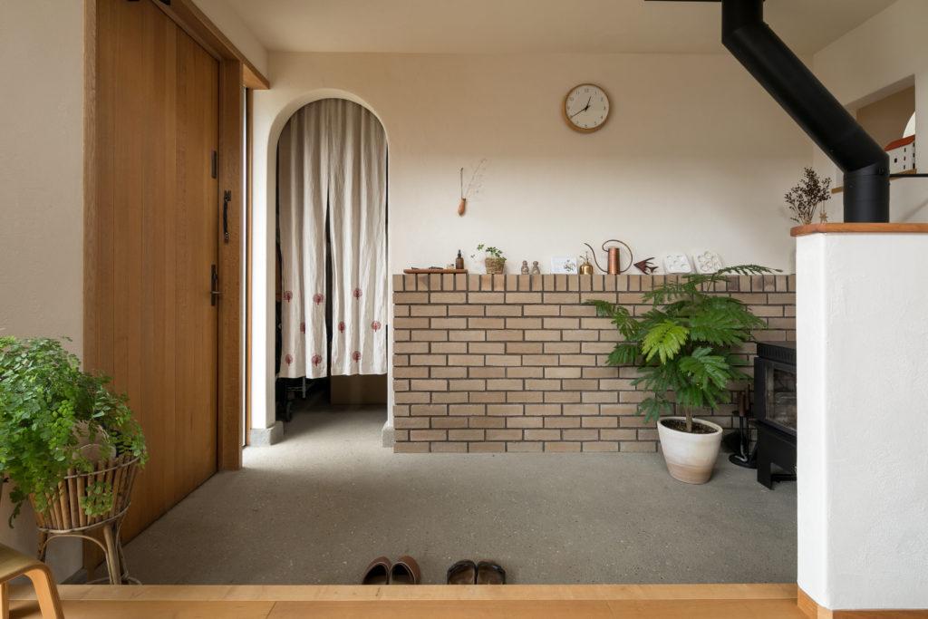 広い土間玄関。アールの下り壁の奥は広いシューズクローゼット。刺繍をほどこしたのれんは恭子さんのハンドメイド。