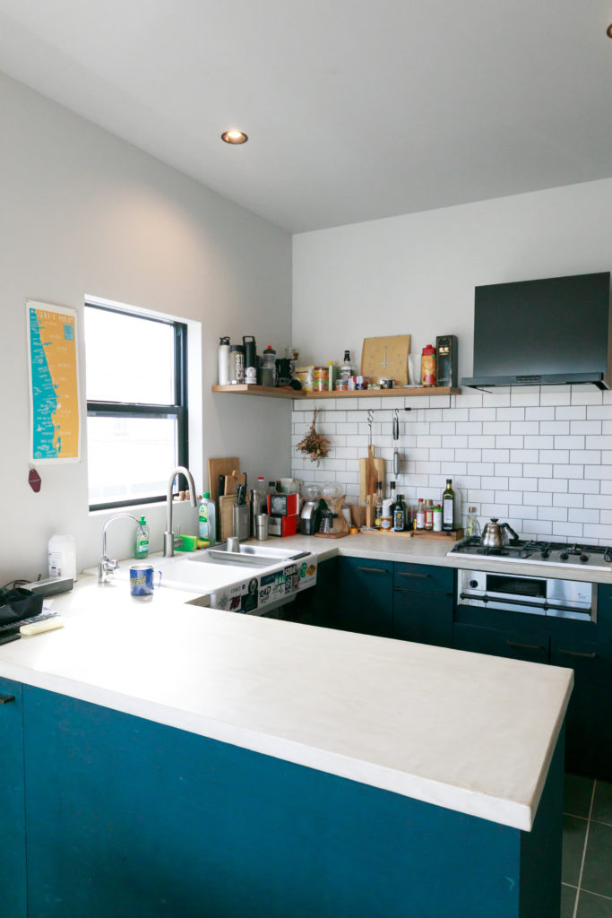 コの字型の大型キッチン。キッチンの天板は防水性の高いモールテックス塗装で仕上げた。陶器のシンクは『IKEA』のもの。