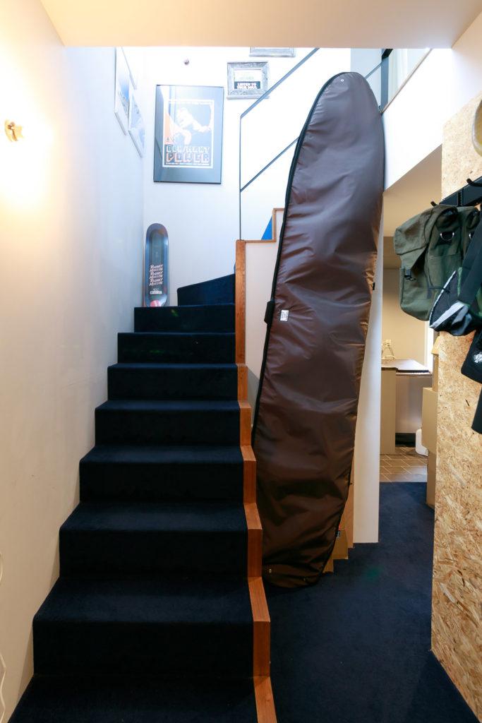 1階は階段も濃いブルーの絨毯を張り込んでいる。「立て掛けてあるロングボードは友人の預かりものです。新居に入らなかったそうです(笑)」