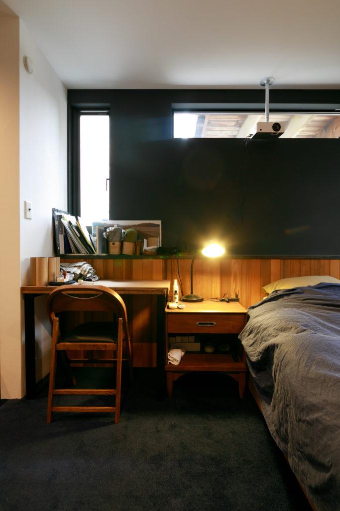 寝室の壁は落ち着いた黒に。ベッドのヘッドボードは板張りにして小物を置けるようにした。