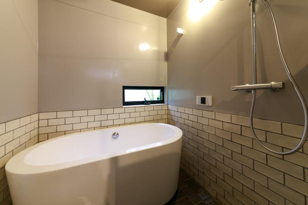 バスルームの壁は下半分をタイル貼りにし、デザイン製の高いバスタブを置いた。