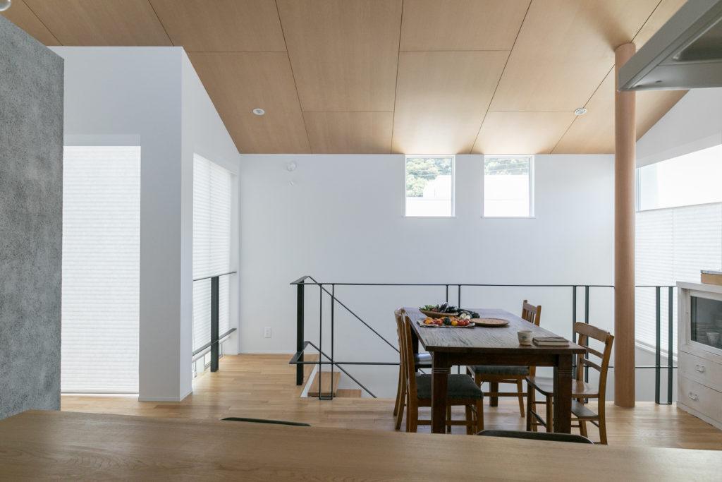 キッチンから吹き抜けの階段ホールを見る。左側にはモルタル仕上げのアクセントウォール。