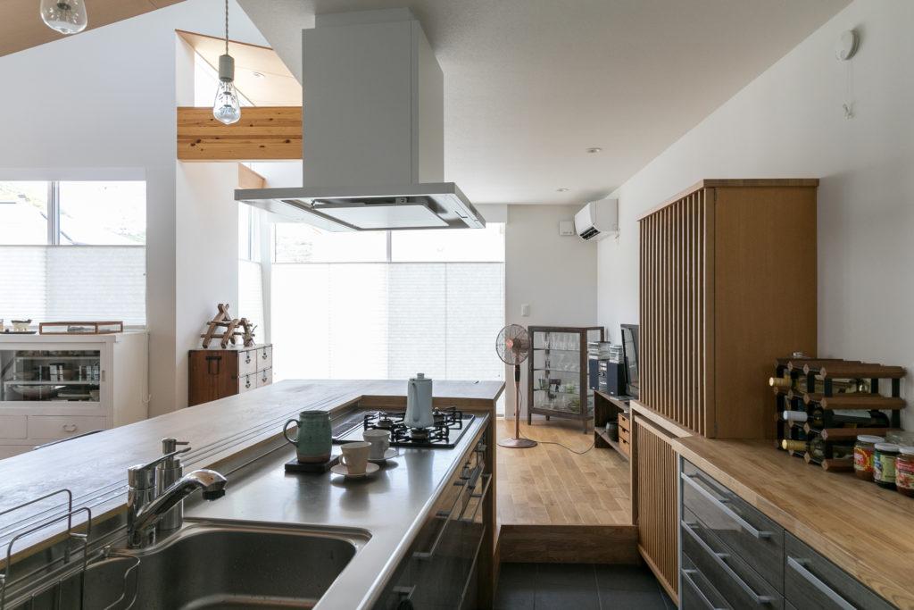 西田さんが特にこだわったオープンキッチン。造作のカウンターテーブルは栓(せん)の木の一枚板から製作されている。ゲストを招いた際は、このカウンターで料理を振る舞うという。また、キッチンの床はゲストと目線が合うように1段下げている。