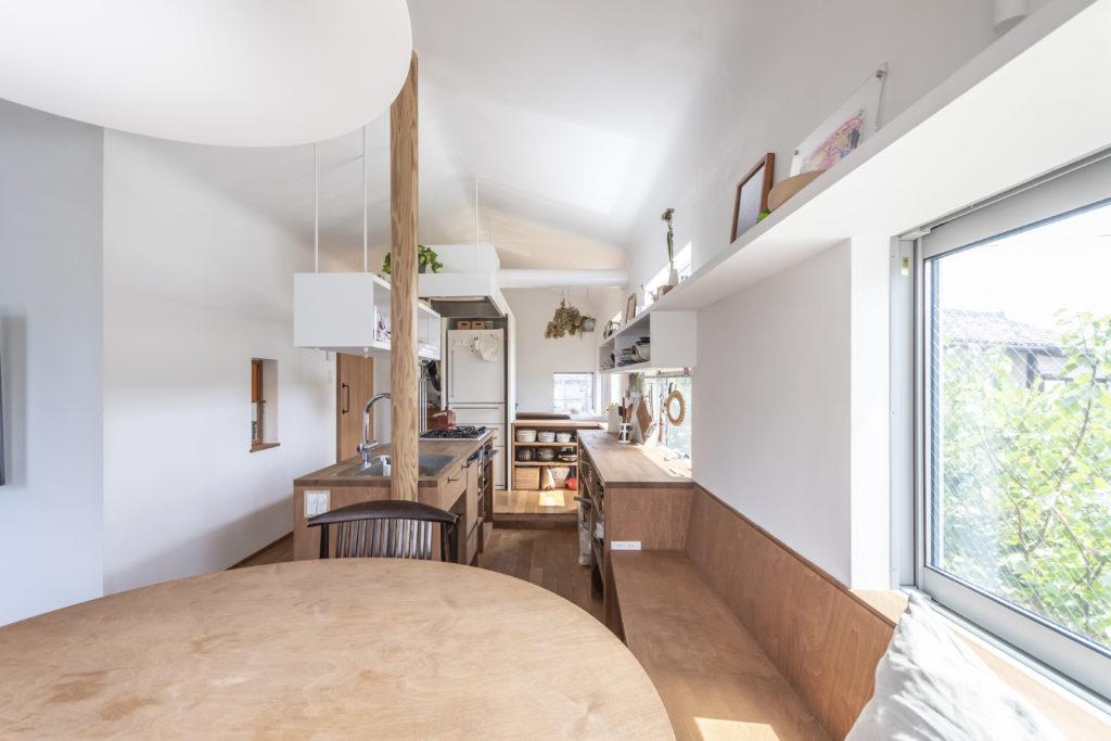 丸テーブルのところからキッチンを見る。天井は家形になりかつ壁との境目が柔らかくあいまいにされている。