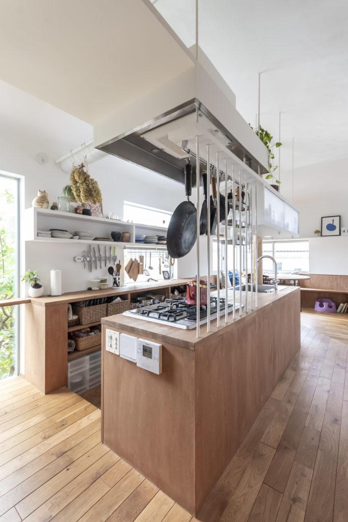 キッチン部分に立てられた白い鉄筋棒が透過性をもちつつ吊り棚とともに通路とキッチンとを仕切っている。