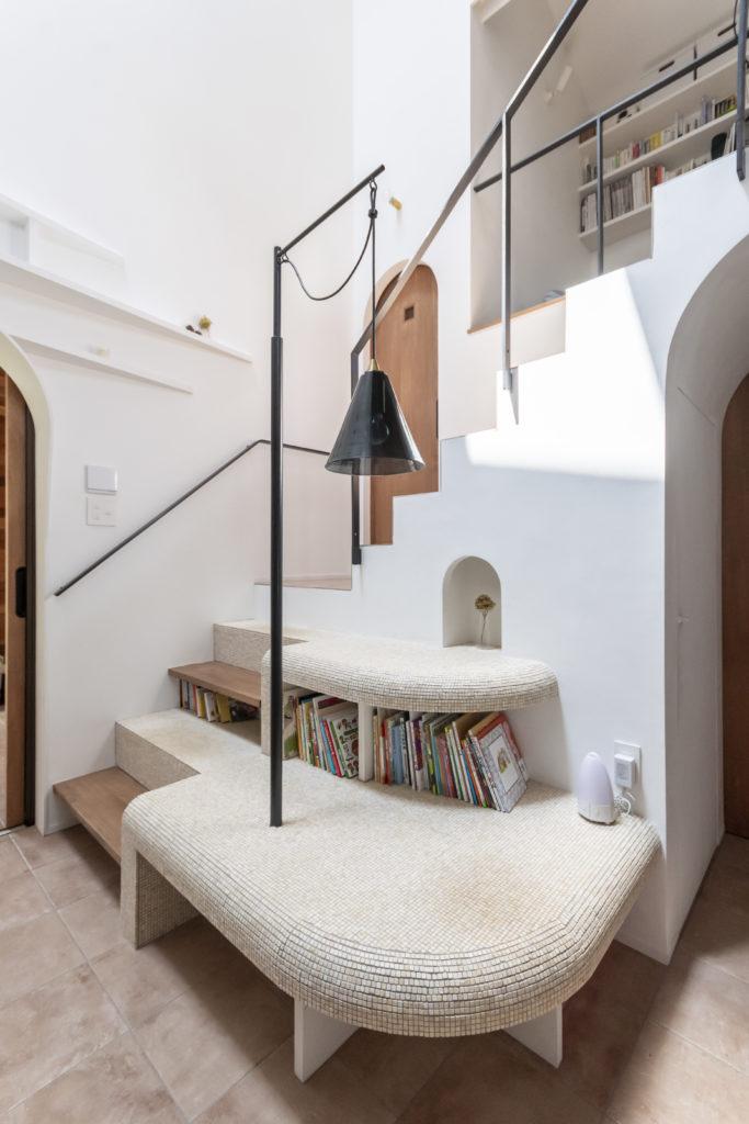 彫塑的、あるいは地形的につくられた階段部分。手前のタイルの部分はお子さんと本を読むスペースにもなっている。