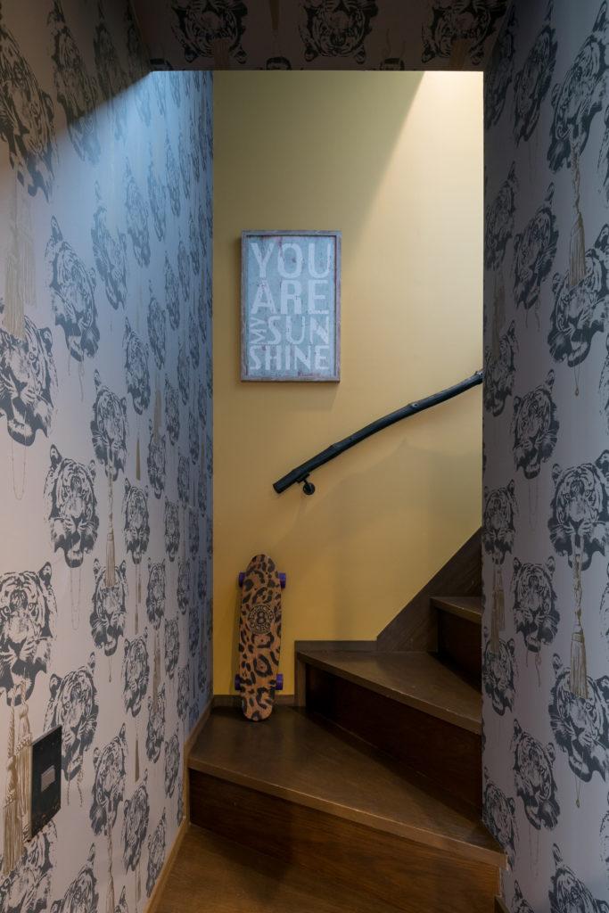 階段の輸入壁紙は虎! よく見ると様々なデザインの金のロープタッセルを咥えている。手摺りは流木。