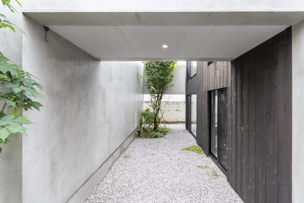 ギャラリーへのアプローチが敷地までのアプローチ部分の細長い道を引き継ぐようにつづく。