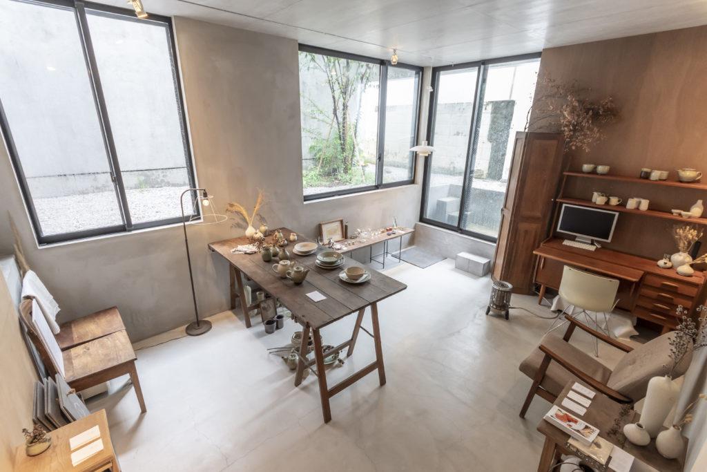 ギャラリーの入口は右の開口。半地下だが、天高が270cmと高めでかつ開口部も大きいため地下というよりも1階のように感じられる。右に置かれた机は田中さんのワークスペースとしても使われている。