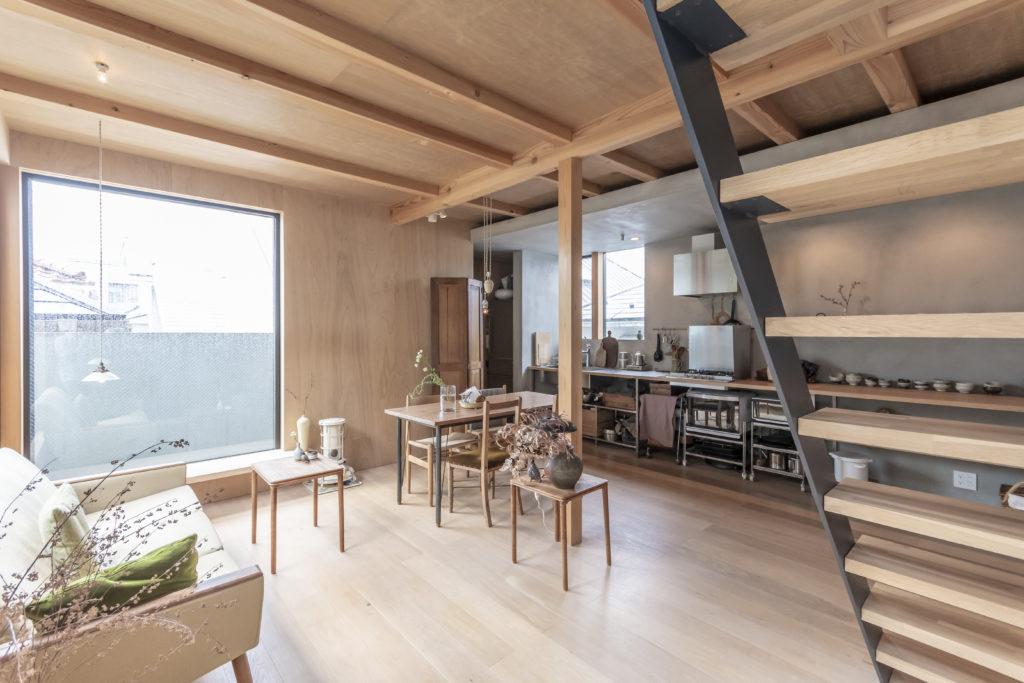 2階への階段下から見る。奥さんは「キッチンを作業場的な見た目にしたいと思った」という。